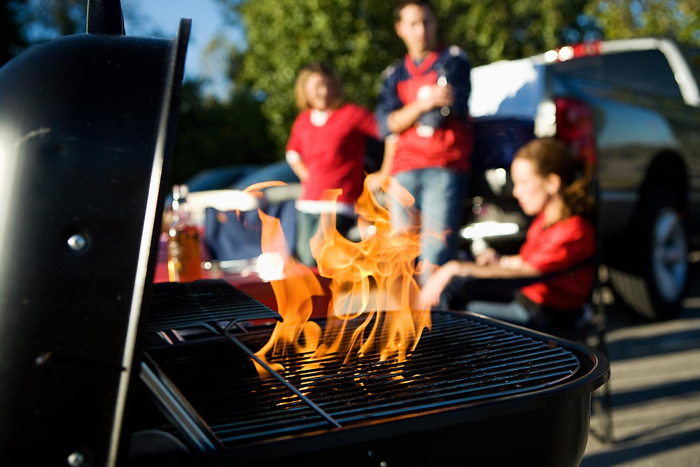 Friends grilling food for a football party in a parking lot, while tailgating.