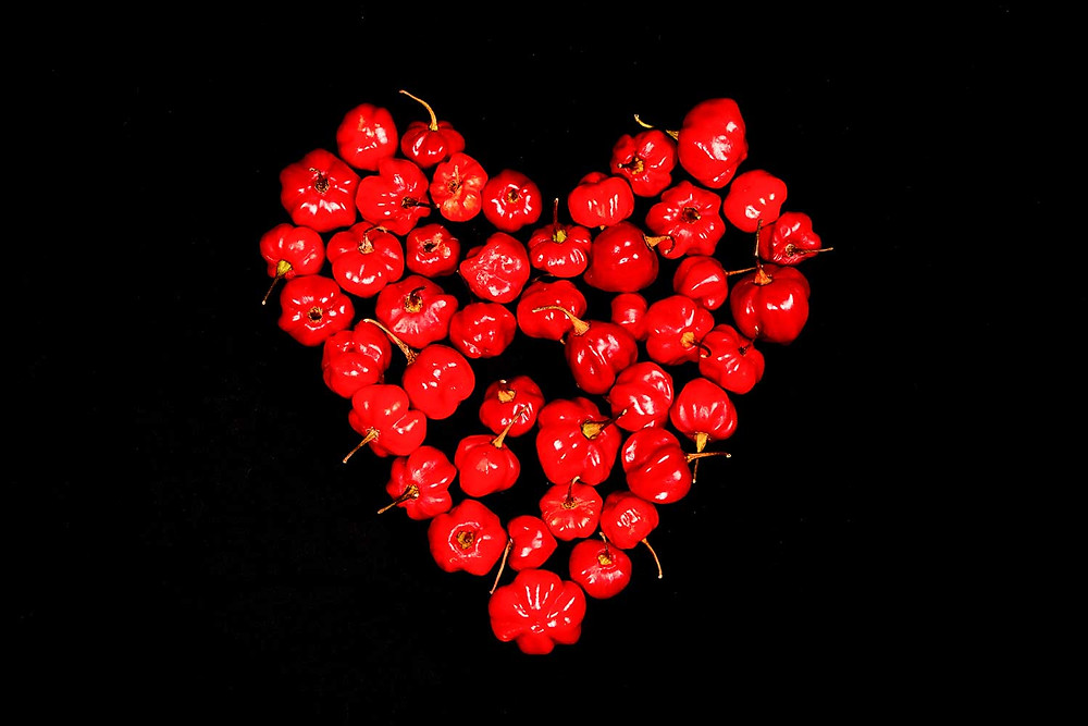 Heart shape formed from many bright red habañero peppers on a black background