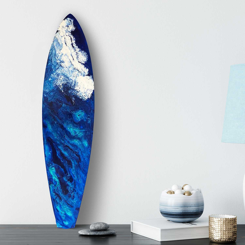 Hand-painted surfboard with blue and white crashing wave, sitting on dresser in ocean themed bedroom