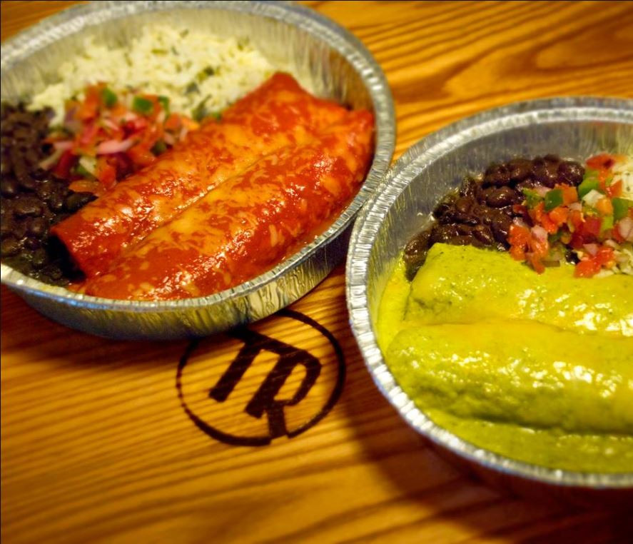 Red and green sauced enchiladas in foil trays on a wooden table from Tortilla Ranch Mexican Grill in Overland Park, Kansas.