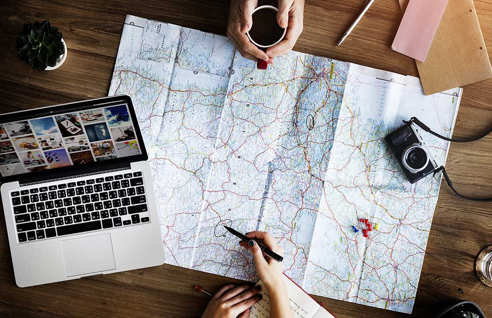 Top view of a map spread on a table, surrounded by travel planning items with two pairs of hands planning an adventure