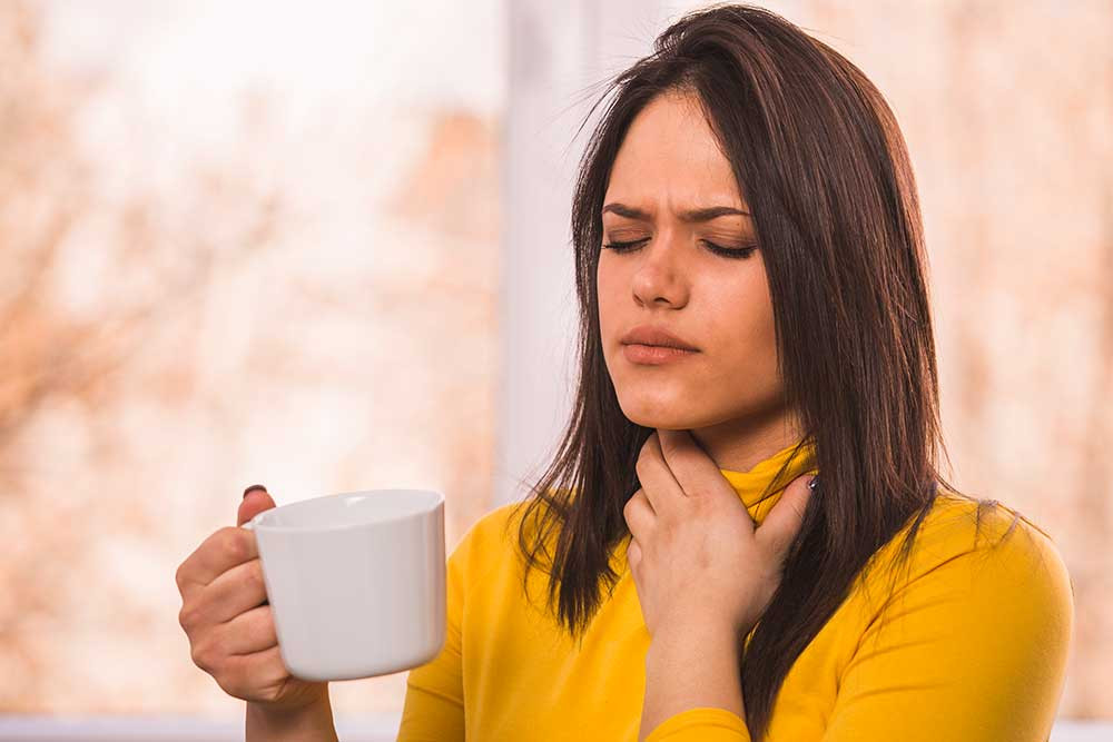 Woman holding one hand to her sore throat, while she holds a cup of soothing hot sauce tea in her other hand.