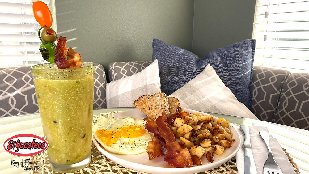 Tall glass of green Bloody Mary beside a full brunch plate in a cozy breakfast nook.