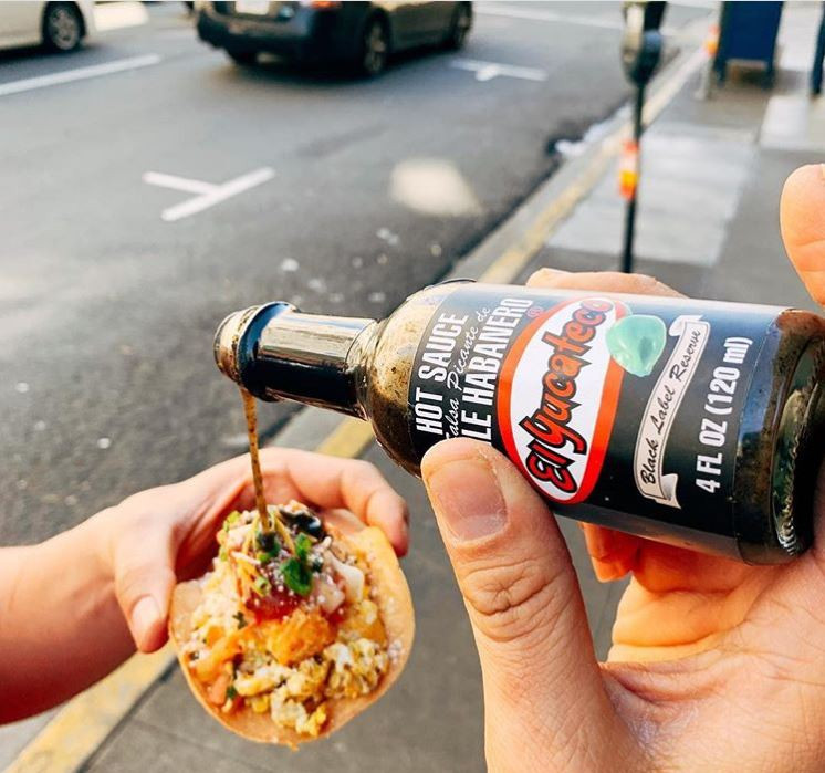 Fresh small taco with a person pouring El Yucateco Black sauce over it, from Tacorea, San Francisco, California.