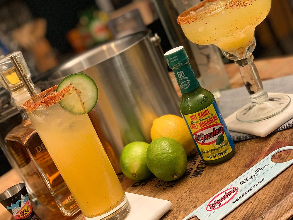 Pale orange Electric Rodeo cocktail featuring El Yucateco Green Habanero Sauce, surrounded by ingredients and bar tools.