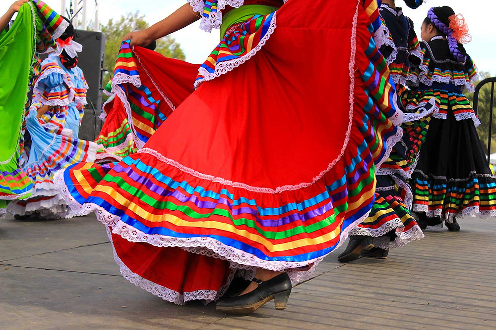 Women dancing to mariachi music in brightly colored dresses to celebrate Cinco de Mayo.