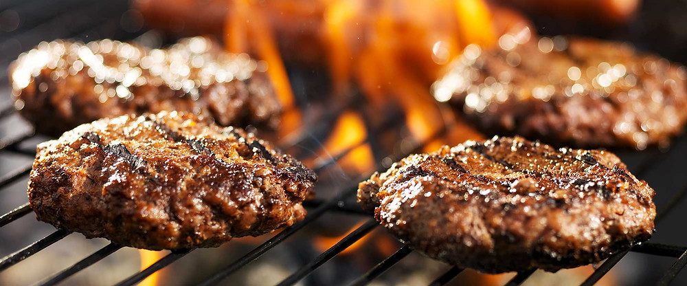 Hamburgers cooking on a fiery grill, with dark grill lines and deliciously crispy looking crust