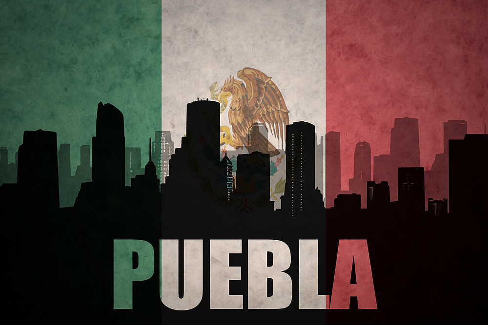 Puebla city skyline silhouetted against the Mexican flag, symbolizing the rallying cry of the battle at Puebla and Cinco de Mayo