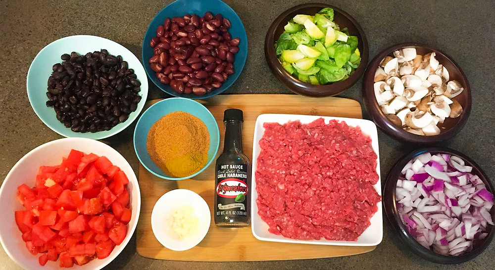 Freshly prepared ingredients for Mexican hot sauce chili, all lined up on a countertop, with El Yucateco Black Label Sauce