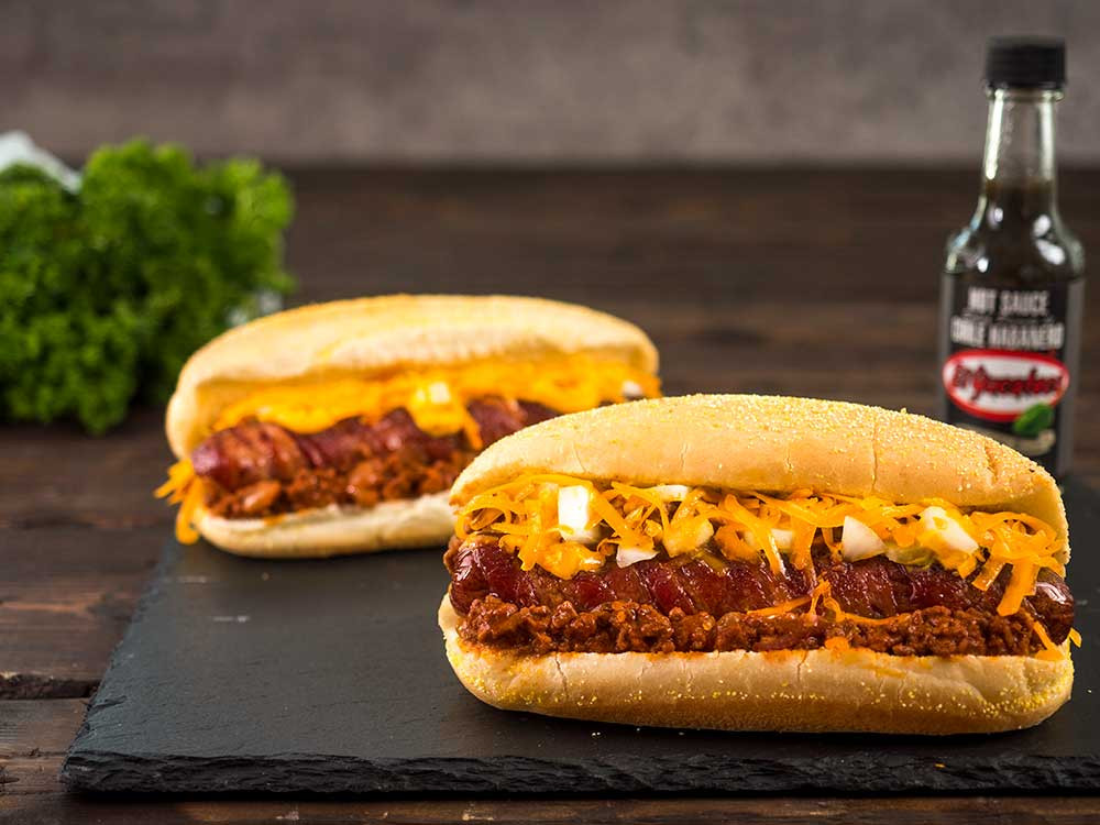 Bacon wrapped chili dogs with cheese and onions beside a bottle of El Yucateco Black Label Reserve Habanero Sauce.