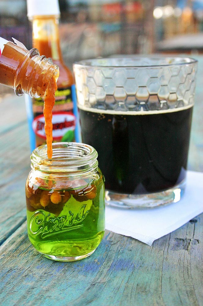 Bright green shot with El Yucateco Hot Sauce next to a pint of dark brown root beer. One of the best drinks for tailgating.