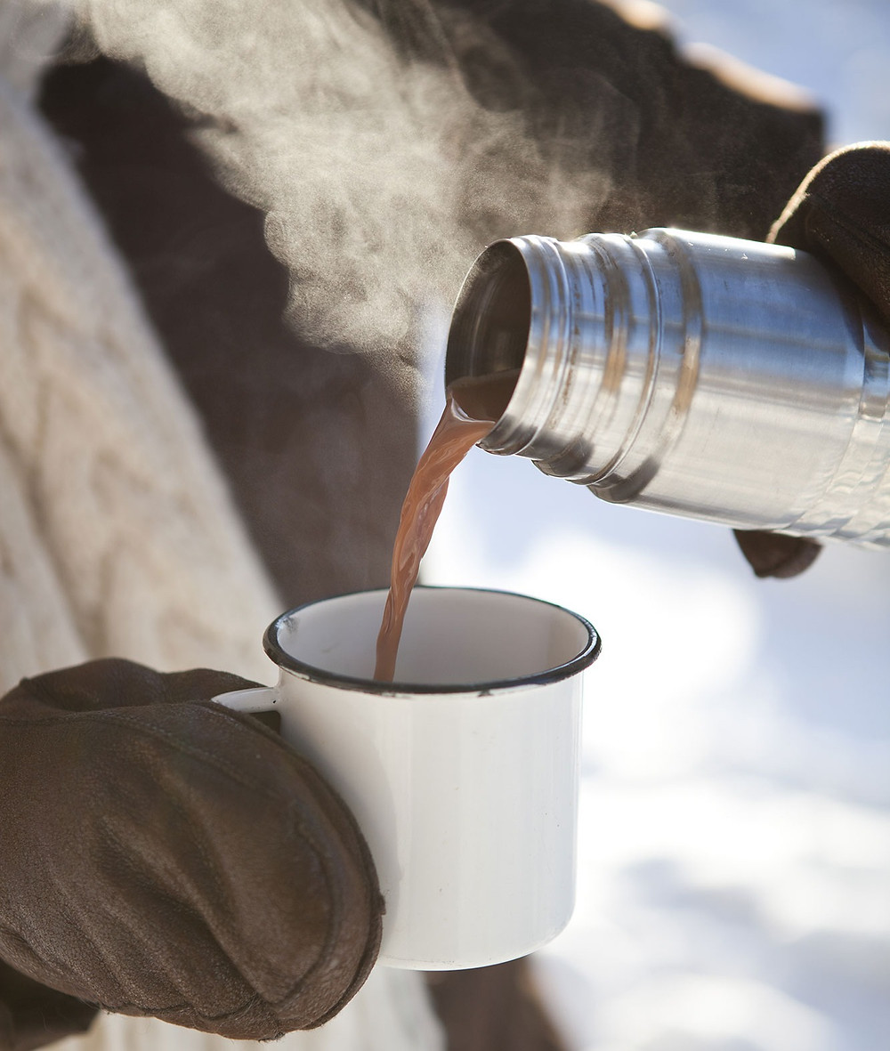 Person pouring steamy mexican spiced hot chocolate from a thermos into a mug at a winter football tailgating party.
