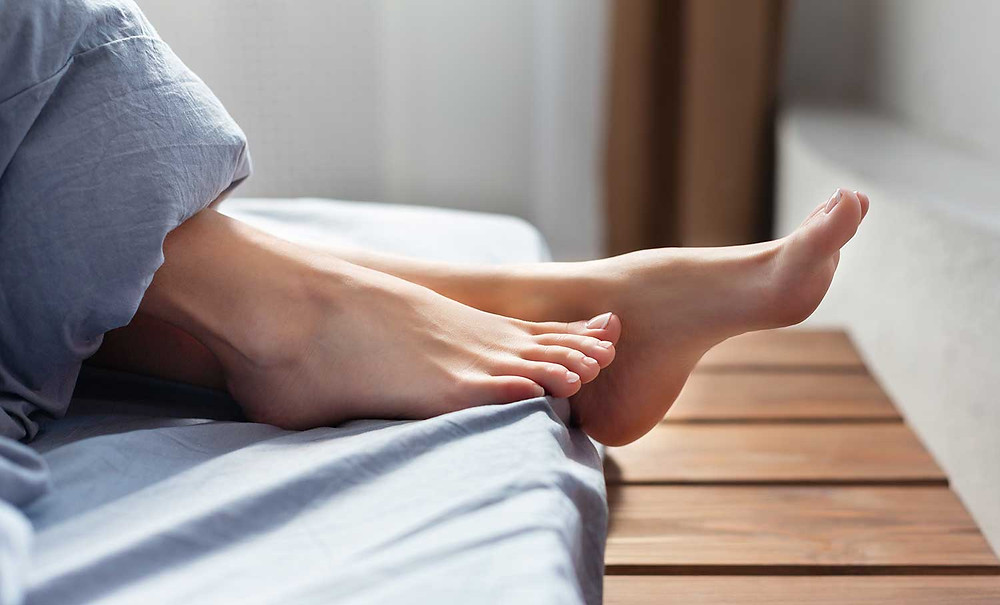 Bare feet sticking out of soft blue covers on a cozy bed