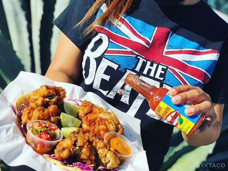 Crispy fried fish with lime and El Yucateco hot sauce being served by a girl with a Beatles shirt in Los Angeles, California.