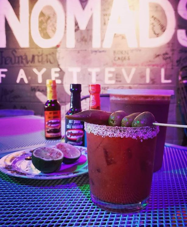 Loaded Bloody Mary with salt rim, olives, peppers, lime, and El Yucateco in front of Nomads' logo wall, Fayetteville, Arkansas.