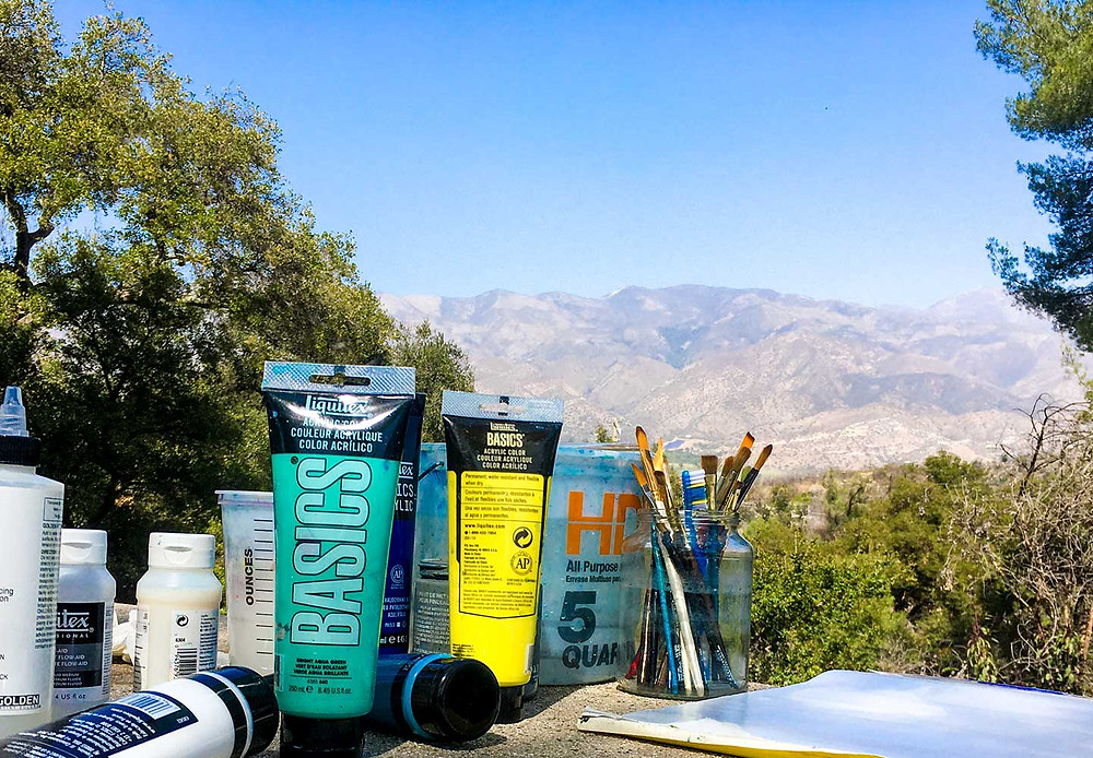 Acrylic paint tubes and artist's brushes sitting on a picnic table with trees and mountains in the background
