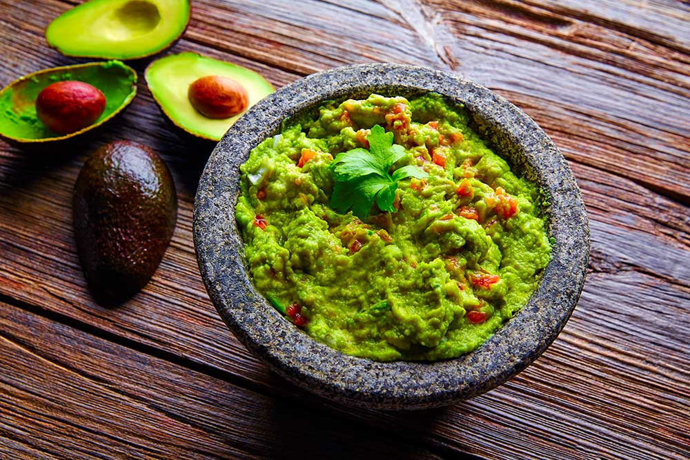 The best guacamole recipe that's easy and simple, but full of spicy El Yucateco flavor. Served in a classic molcajete and garnished with a sprig of fresh cilantro.