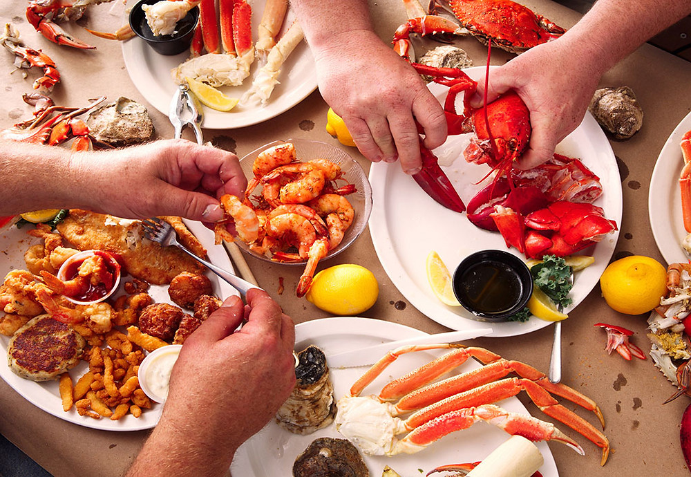 Table full of seafood being enjoyed by busy hands, including lobster, shrimp, crab, and more.