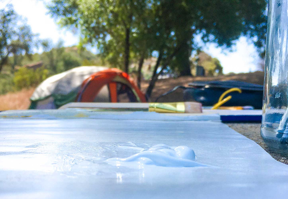 White puddle of paint and artist's brush close to the camera, with a camping tent and trees slightly blurred in the background