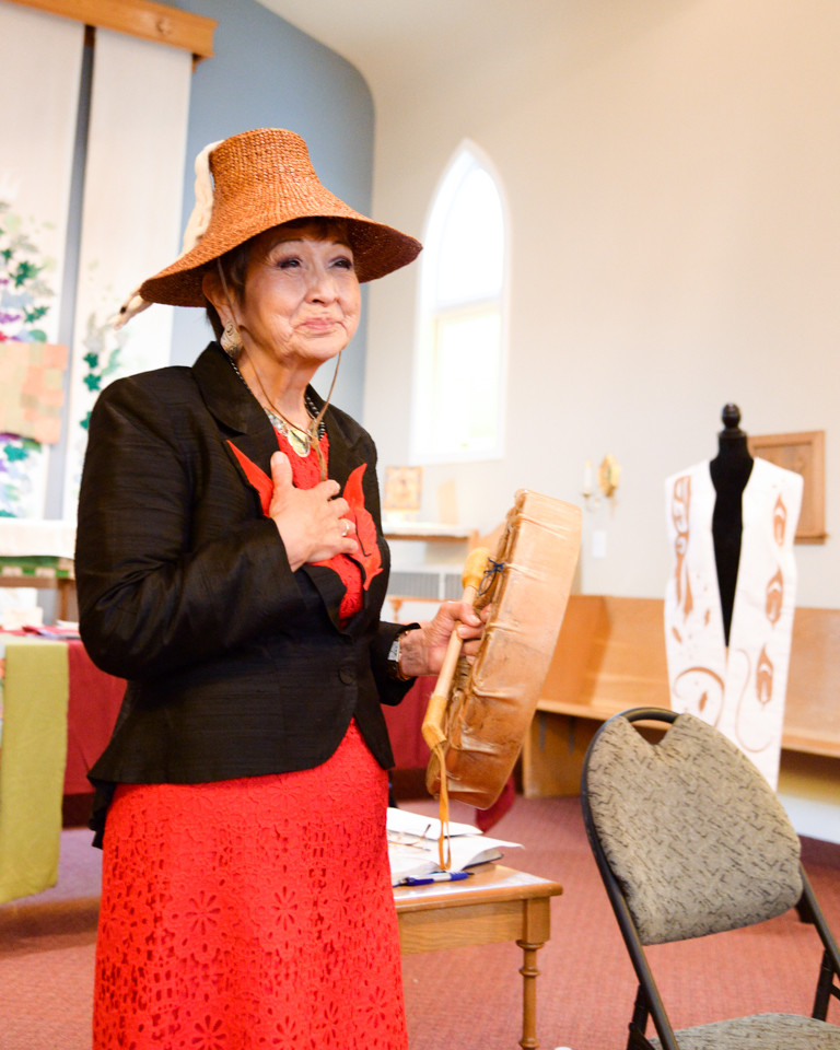 Indigenous artist standing with her hand on her heart, holding a ceremonial drum, wearing Coast Salish woven cedar hat, welcoming participants to Feather Dance.