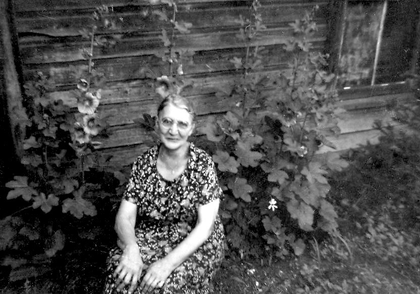 Woman sitting in front of Hollyhocks