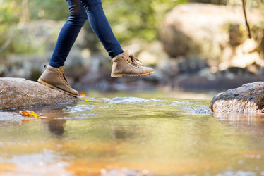 young woman hiking in mountain crossing stream.jpg