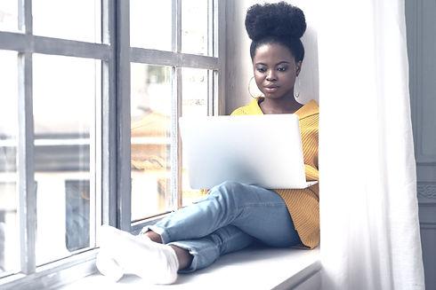 black-woman-sitting-on-windowsill-workin