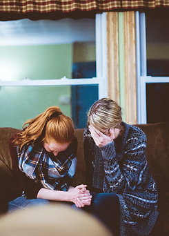 Grief Counselling - Two women holding hands on a couch crying after a loss.