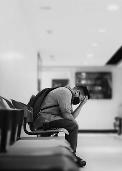 Depression Counselling - depressed looking masked man in a waiting room with his hand on his forehead