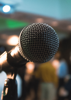 Workshops and Presentations - images of a microphone in front of a group of people.