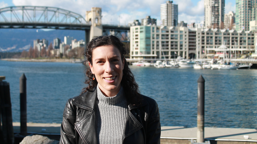 Myriame Lyons, Vancouver Counselling Therapist, sitting by the sea with the Burrard Bridge in the background