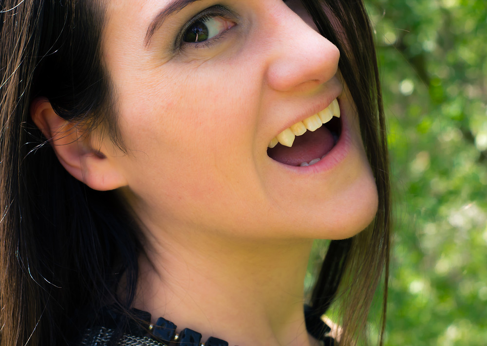 A female vampire smiles at the camera.