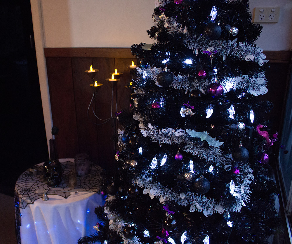 A very gothic Christmas tree, decorating in ghostly lights and glittery spiders.