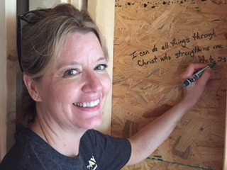 Sister writing scriptures on wood framin