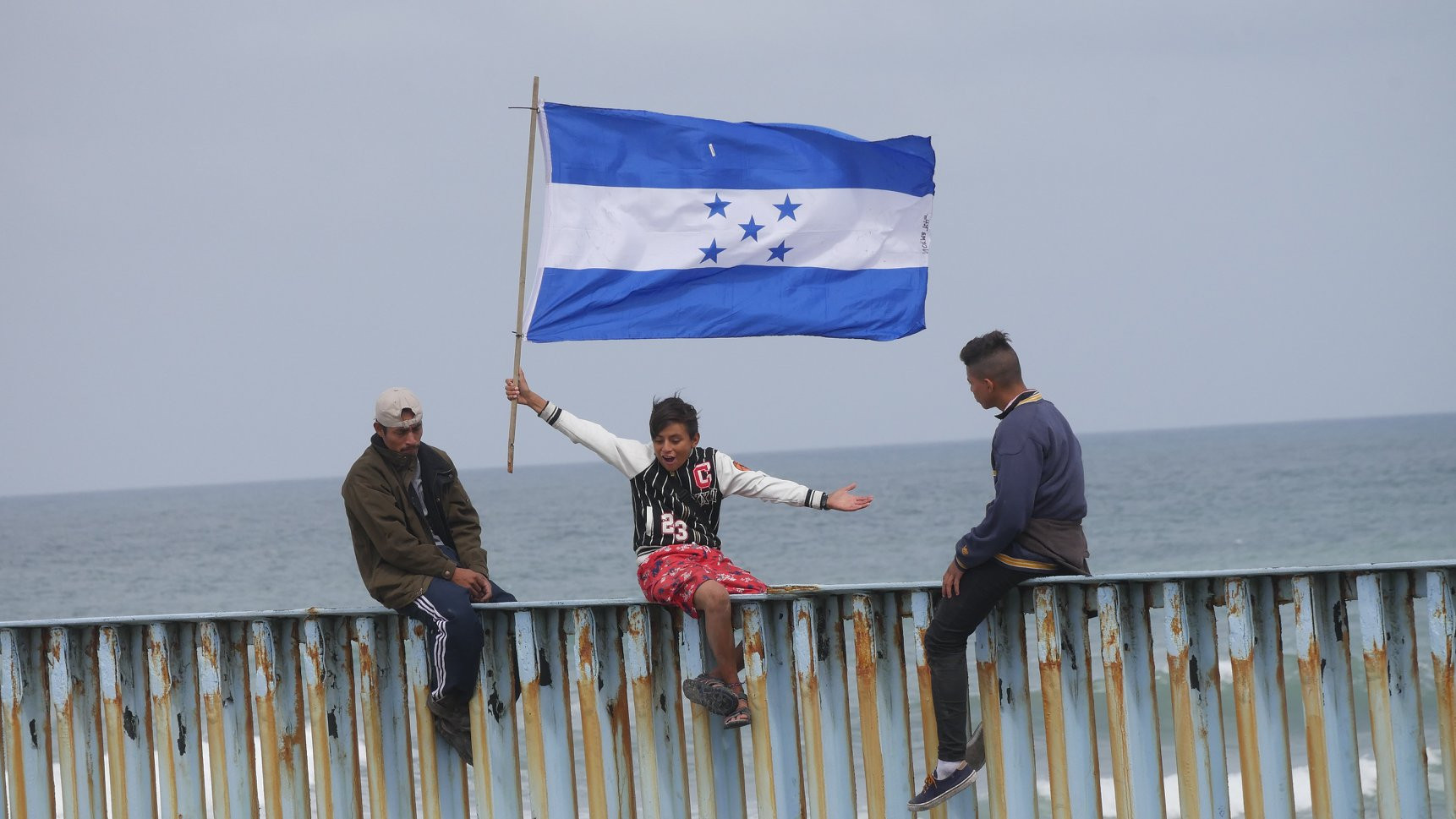 Child part of migrant caravan on border wall waving Hondurus flag
