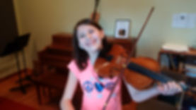 A student smiles and holds a violin