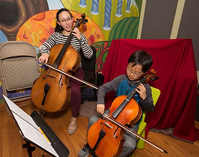 A student and teacher both play the cello