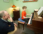 A student playing piano while a teacher observes