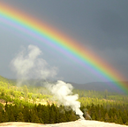 A Rainbow over Old Faithful, one of the best things to see in Yellowstone with kids