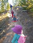 A line of kids hiking on a Yellowstone hiking trail
