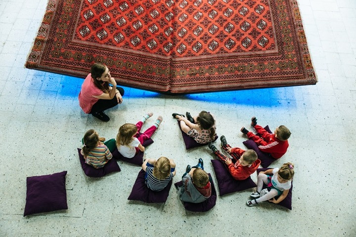 Image shows a large area rug folded up like a book. There is a woman and 8 children sitting on purple cushions looking at the rug like they are reading a book