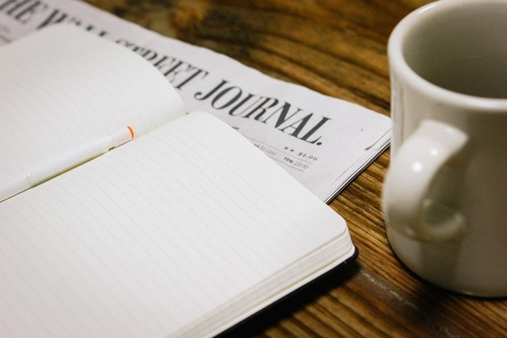 Picture of an open journal with a pen, an issue of the wall street journal and a white mug on a wooden table