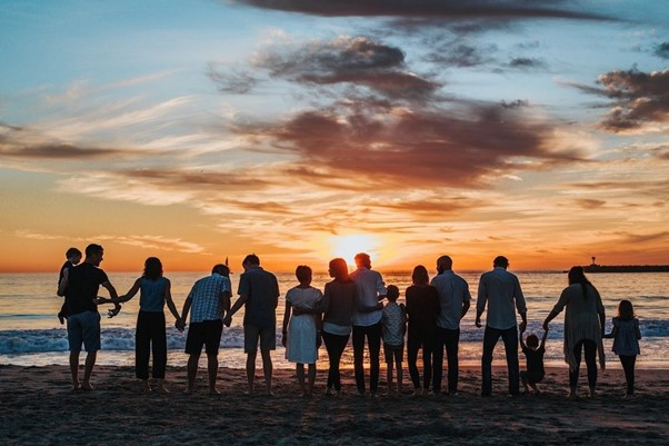 Picture of a group of adults and children standing on a row in the beach, either holding hands or standing together facing the sea and sun set with their backs to the camera.