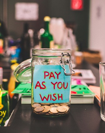 Picture of a jar of coins with the words Pay as you wish written on it. The background of a shop is blurred