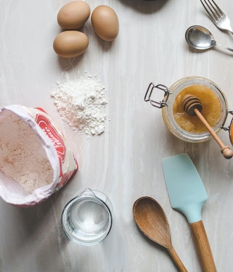Picture of various baking ingredients and utensils on a table. There is an open bag of flour with a small pile of flour on the table, 3 eggs, a fork and spoon, an open jar of honey, a measuring jug full of water, a wooden spoon and a spatula