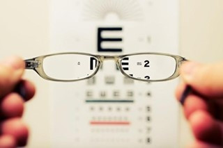 Picture of someone's hands holding a pair of grey small framed glasses. There is a sight test chart which is blurred and out of focus except for the second line which can be seen through the glasses.