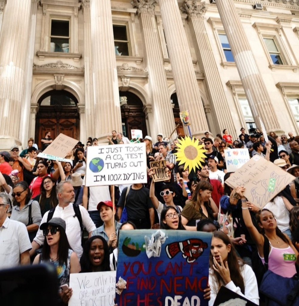 Picture of people protesting climate change inaction outside of a white government building. They are all holding signs and chanting.