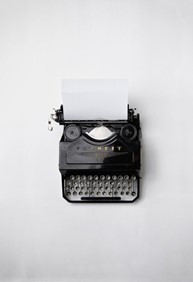Picture of a black typewriter with silver keys and a blank piece of paper sitting in it taken from above. The background is completely white.