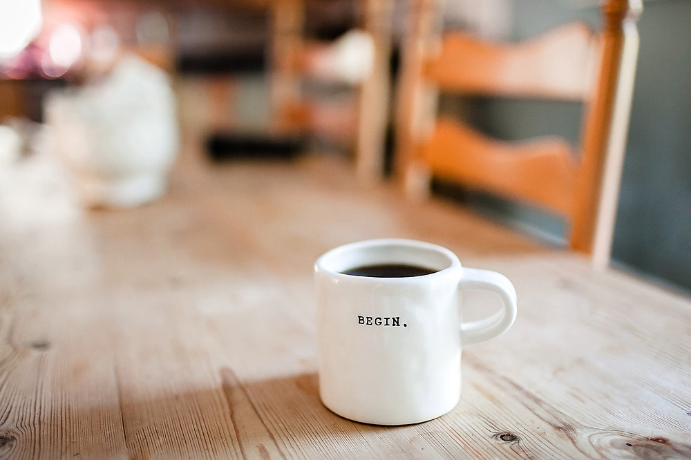 Picture of a full white cup of coffee with the word begin written on it in back text. The background of a wooden table and chairs is out of focus.