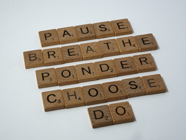Picture of 5 words made out of wooden scrabble pieces: pause, breathe, ponder, choose, and do